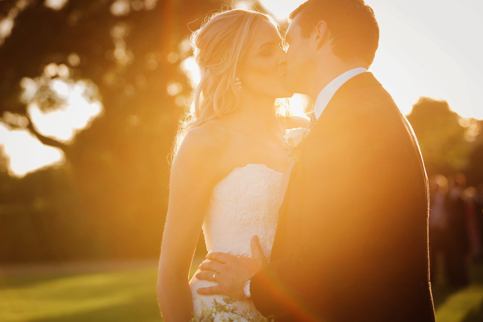 Stunning photo of the bride and groom sharing a kiss at golden hour with extreme golden sun flare at this Goodwood House wedding