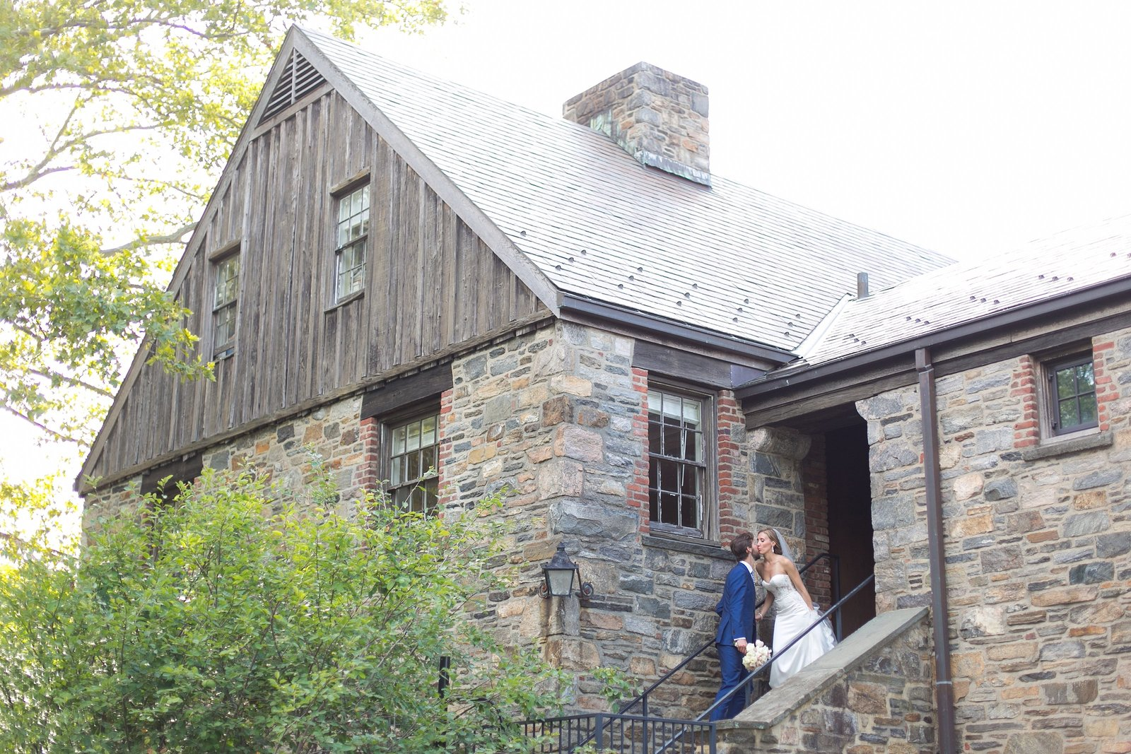 Bride and Groom kissing in front of stone barn from far away at Blue Hill Stone Barn wedding in Westchester, New York Photo