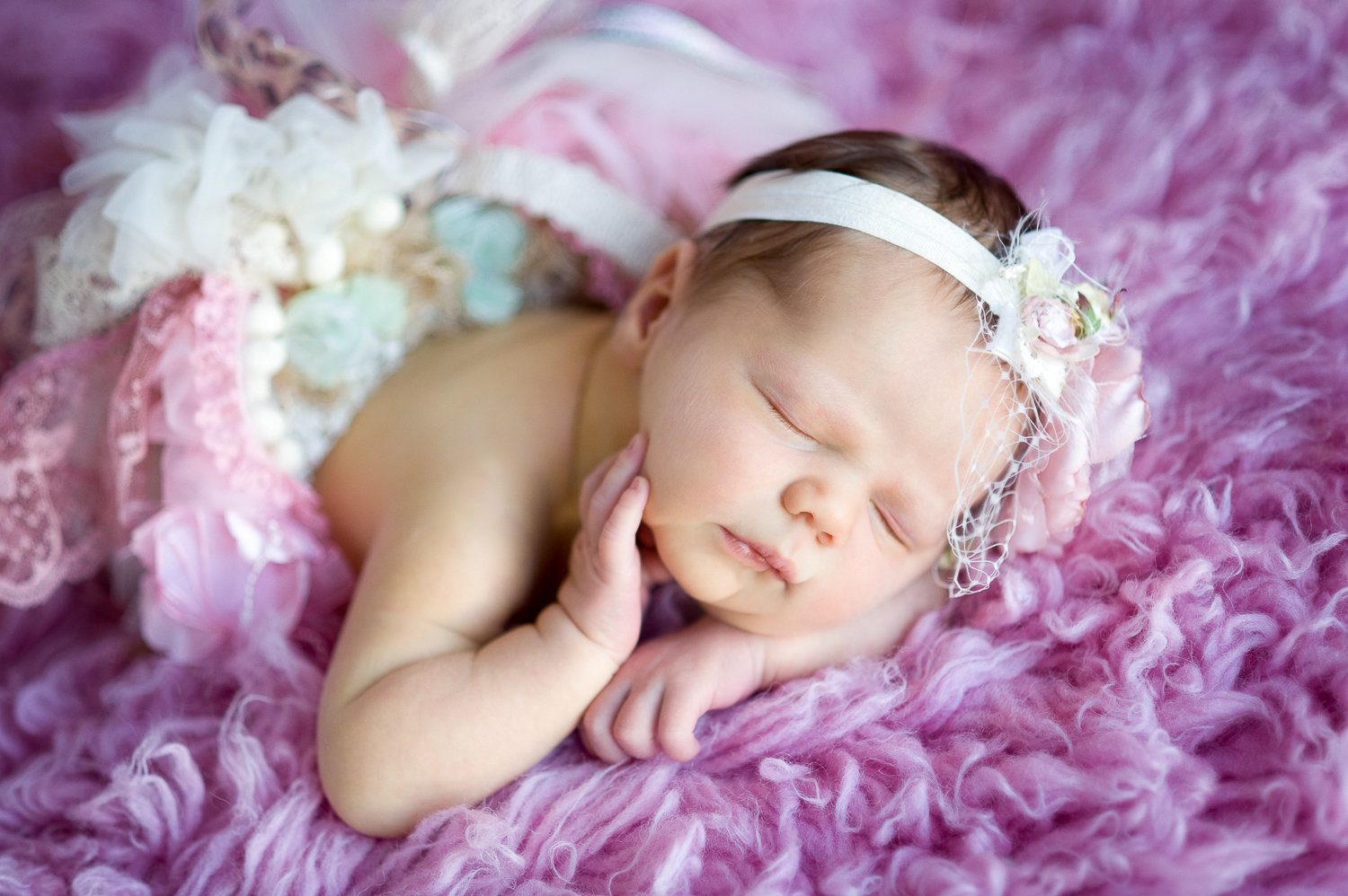 newborn with pink tutu and matching headband and pink flokati rug