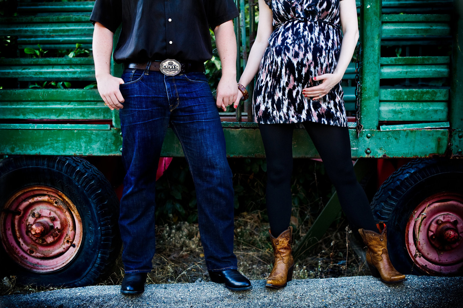 couple wearing cowboy boots for outside maternity photography in San Juan Capistrano
