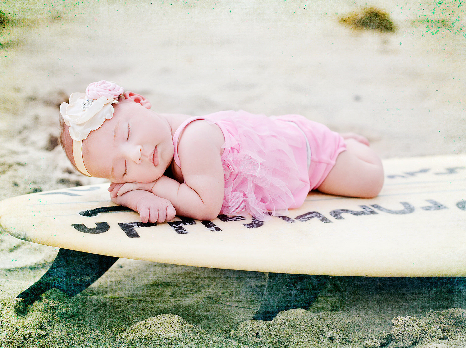 newborn wearing pink bathing suit sleeping on surf board at San Clemente Pier