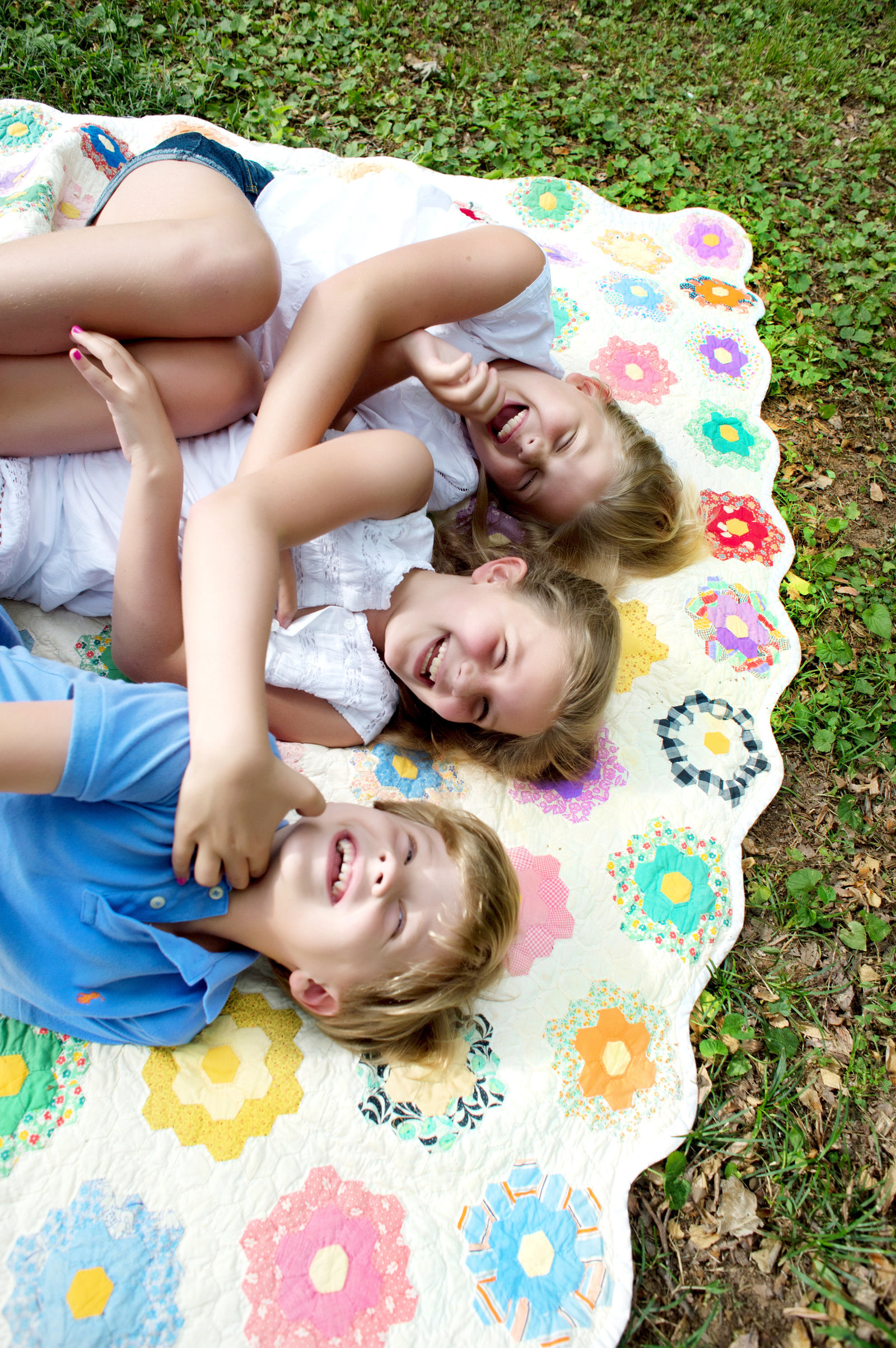 siblings laugh as tickle each other as they lay in the grass on a colorful quilt