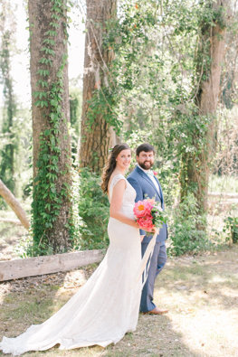 Bride and groom in forest at Adam's Pond in Columbia SC smiling with bouquet