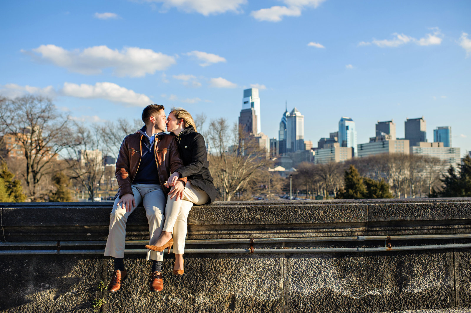 A couple in love sit on the wall of the Philadelphia Art Museum with the center city skyline behind them.