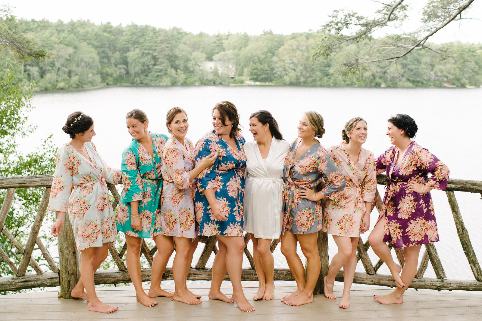 bride and bridesmaids in floral robes standing in front of lake