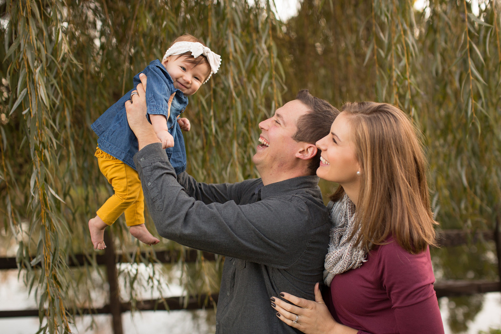 Father lifts smiling baby into air with mother looking