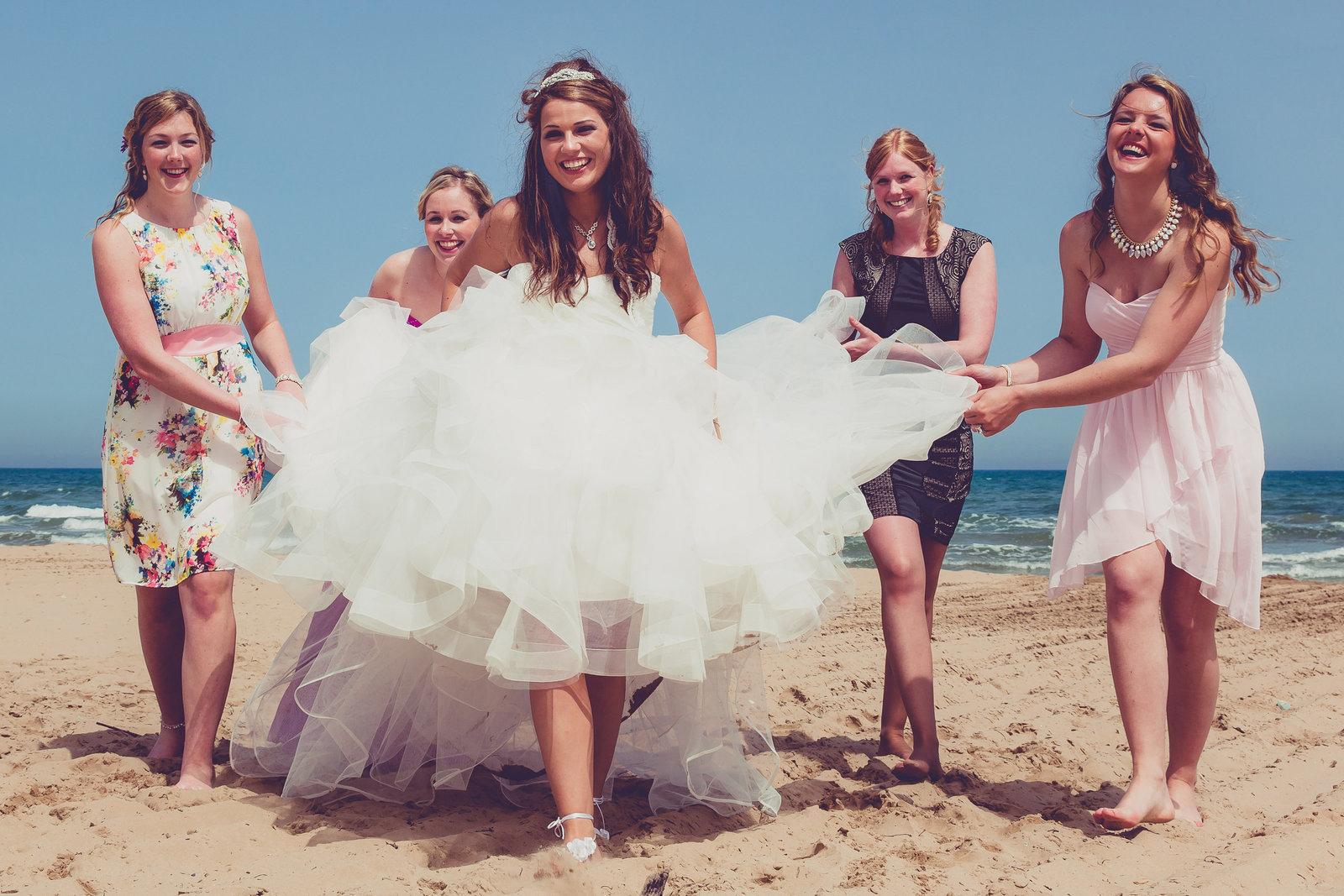 Hoe vrolijk is deze bruid met haar vriendinnen op et strand. Een bruiloft in Italie. Italian beach wedding. Copyright Nanda Zee-Fritse | FOTOZEE
