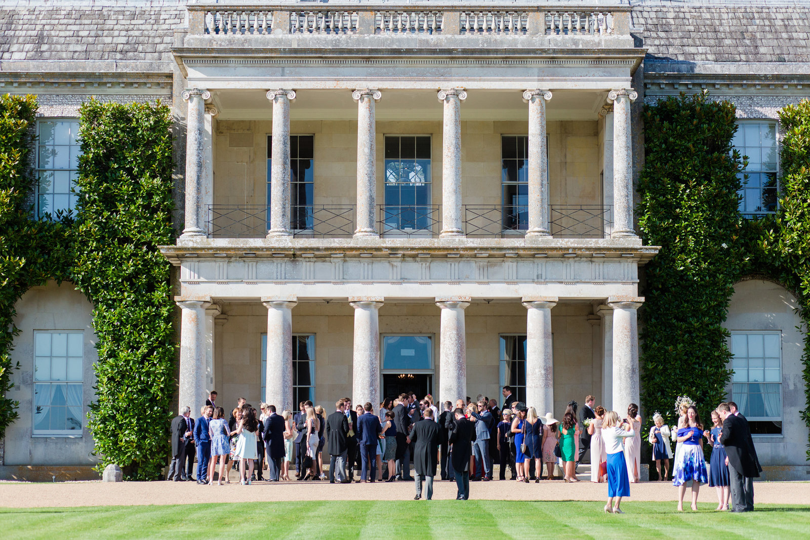 The entire wedding party enjoying a wedding day at Goodwood House at the end of the summer season