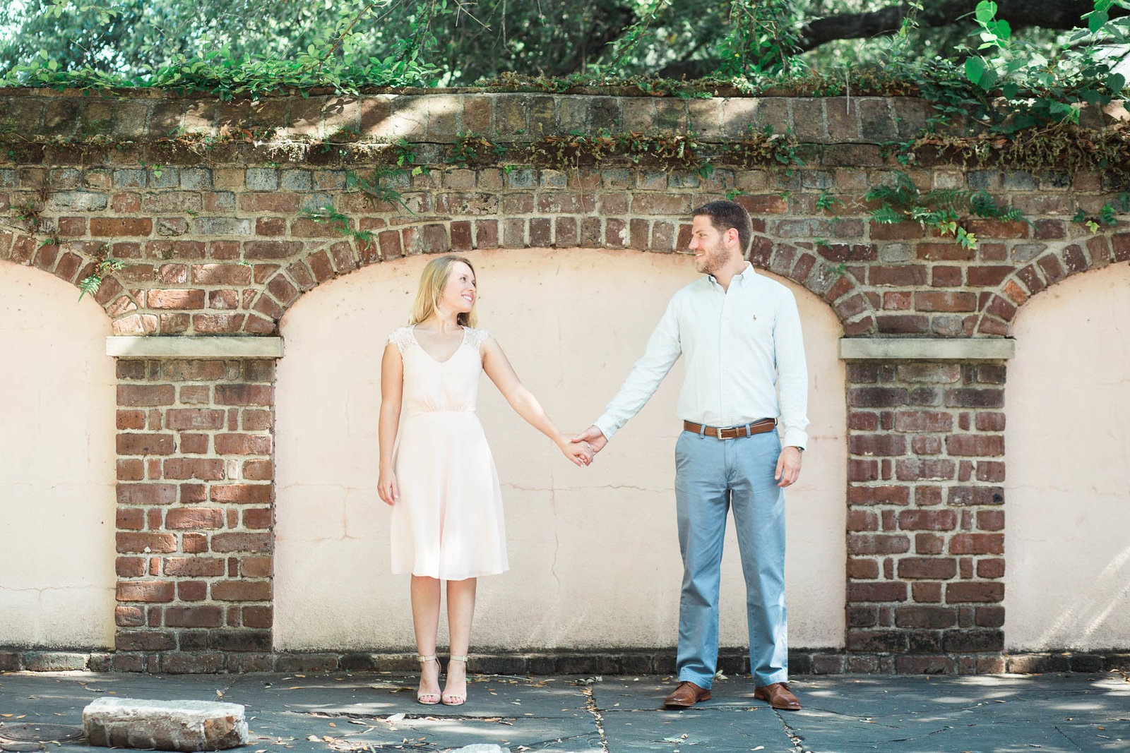 Engaged couple stands in front of brick wall, Downtown Charleston, South Carolina