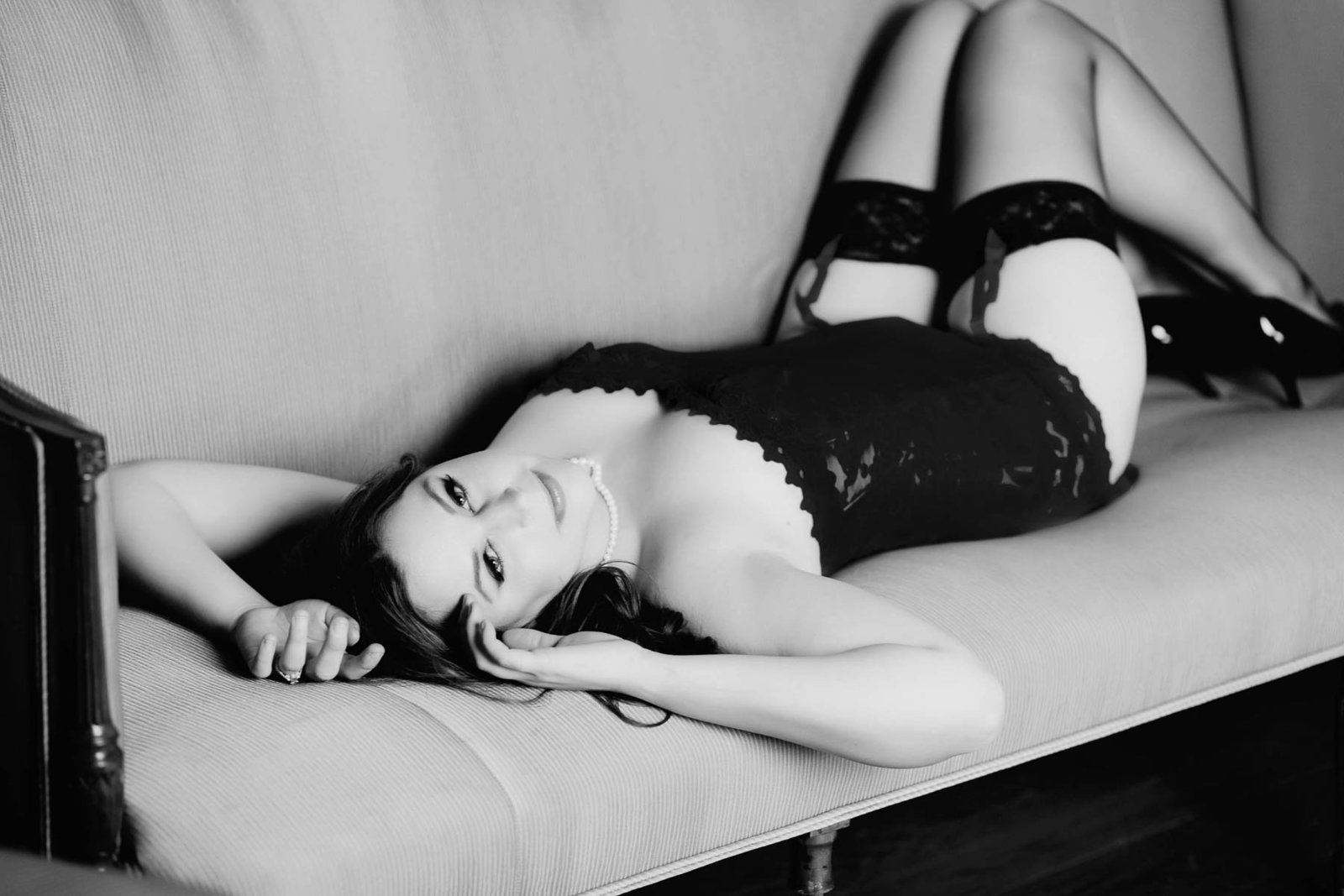 Ms M lays on vintage sofa in her red corset, garter belt and black stockings, Boudoir Photography, Charleston, SC
