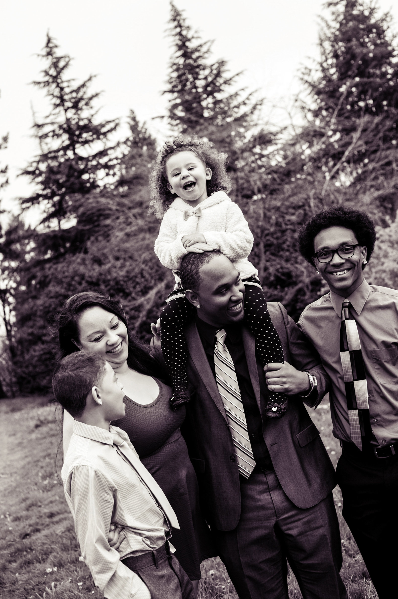 a family of five hug and laugh at each other at hoyt arboretum