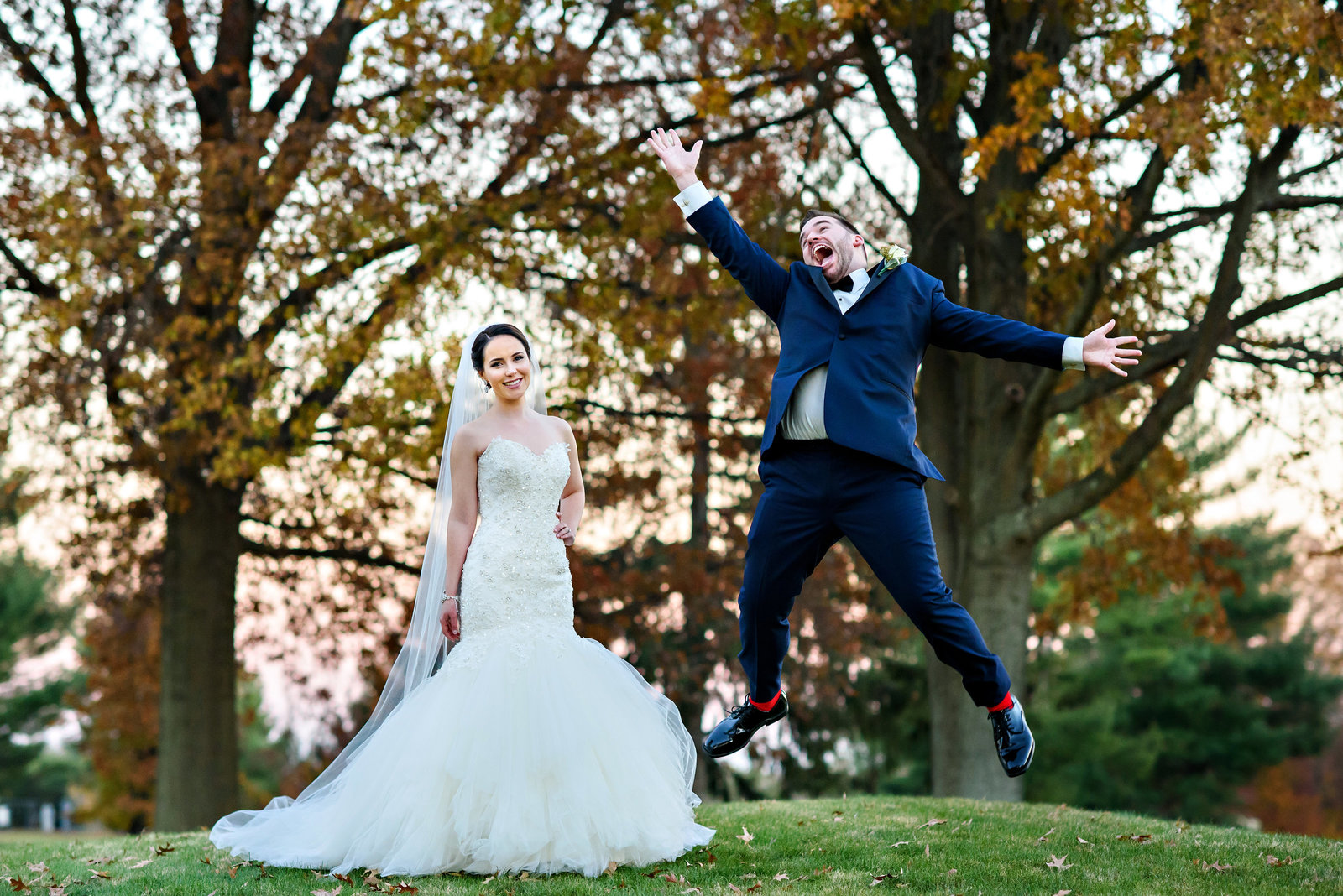 A groom jumps for joy while his bride laughs with excitement at their Northampton Valley Country Club Wedding.