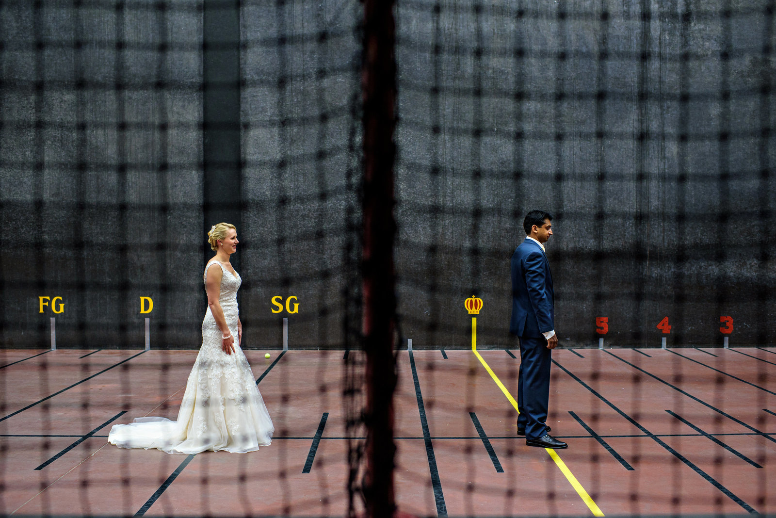 A bride and groom have their first look on an inside tennis court before their wedding.