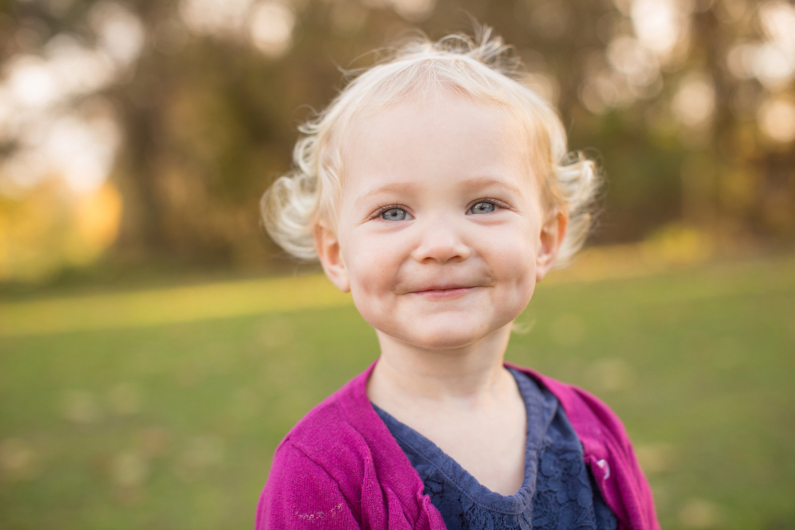 little girl poses for photo outside and smiling