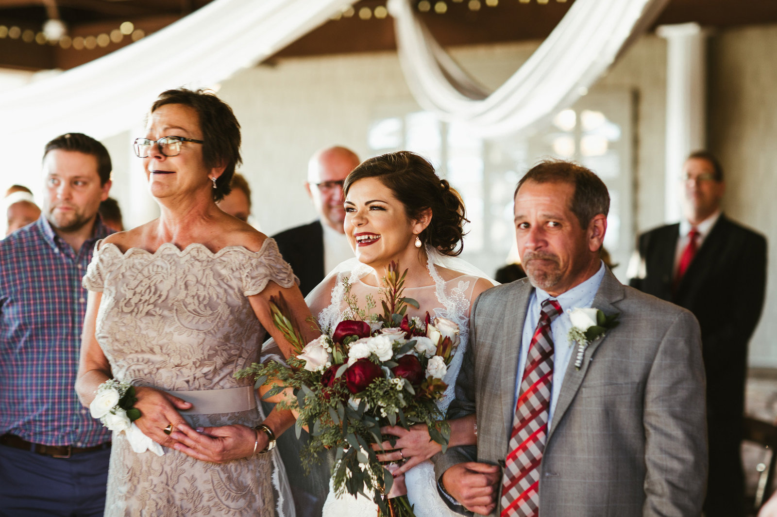 Bride walking down the aisle with her mother and father laughing and crying
