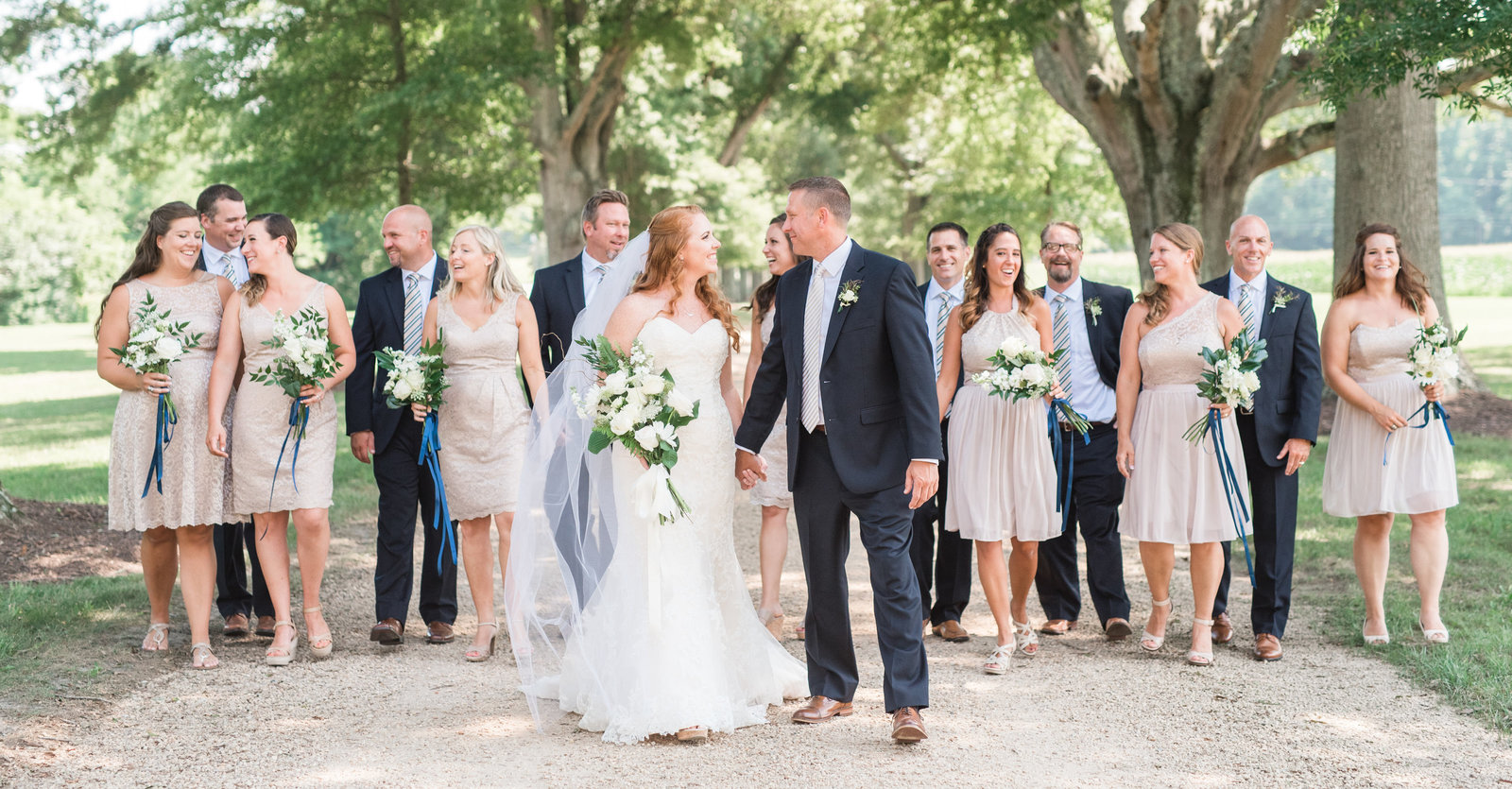nuetral southern wedding party colors on tree lined driveway at historic virginia plantation