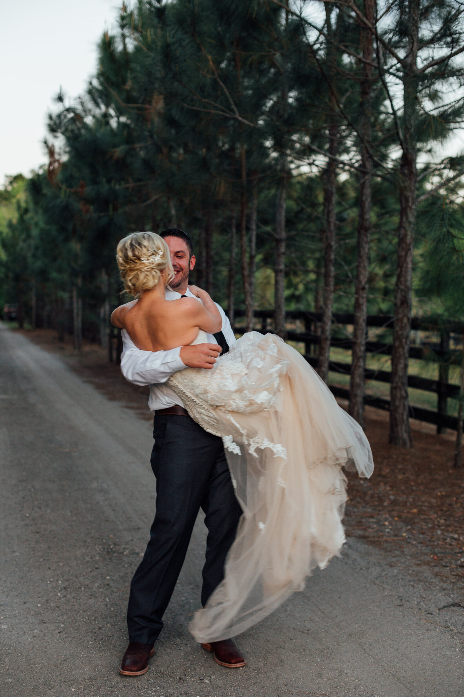 groom-holding-bride-on-country-road-photo-iris-and-urchin-ryley