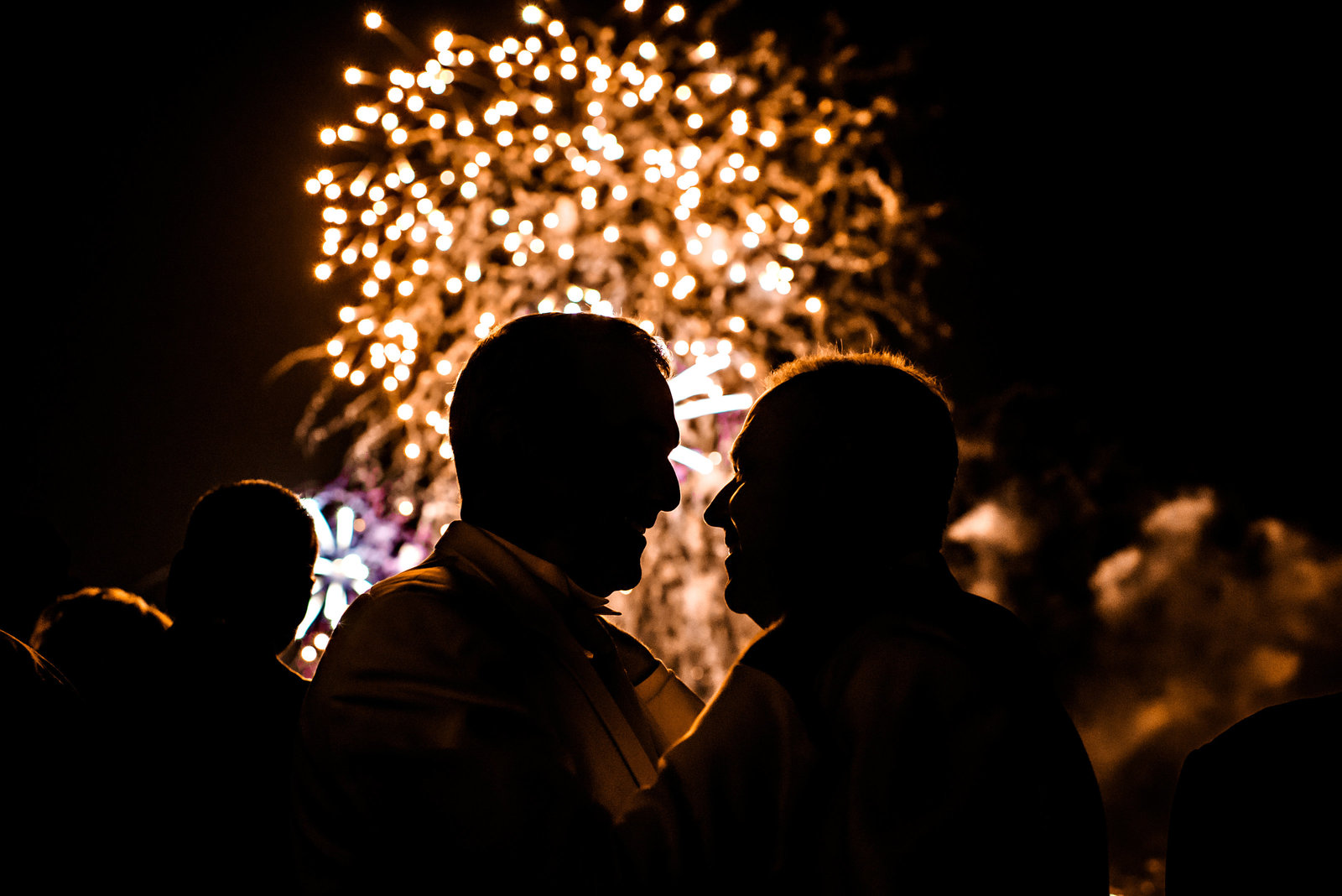 Fireworks light up the night sky and silhouette these two grooms on their wedding day at the Hilton Penns Landing.