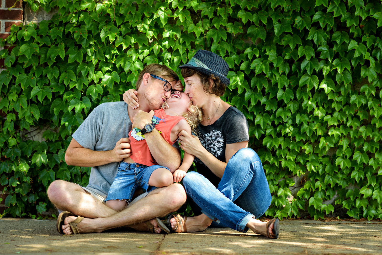 Parents kiss their laughing son in front of an ivy wall in Philly.