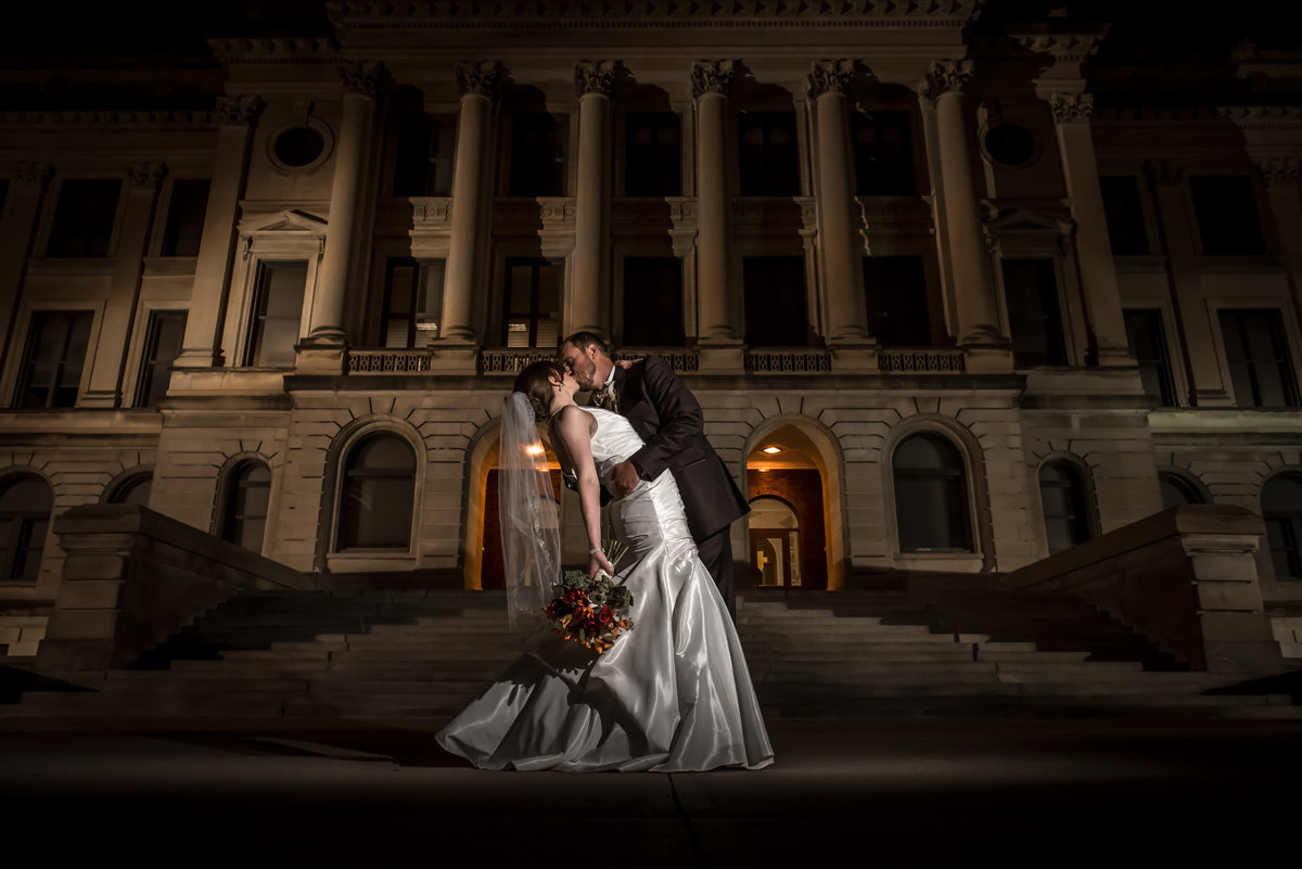 bride and groom kiss in front of omaha central high school