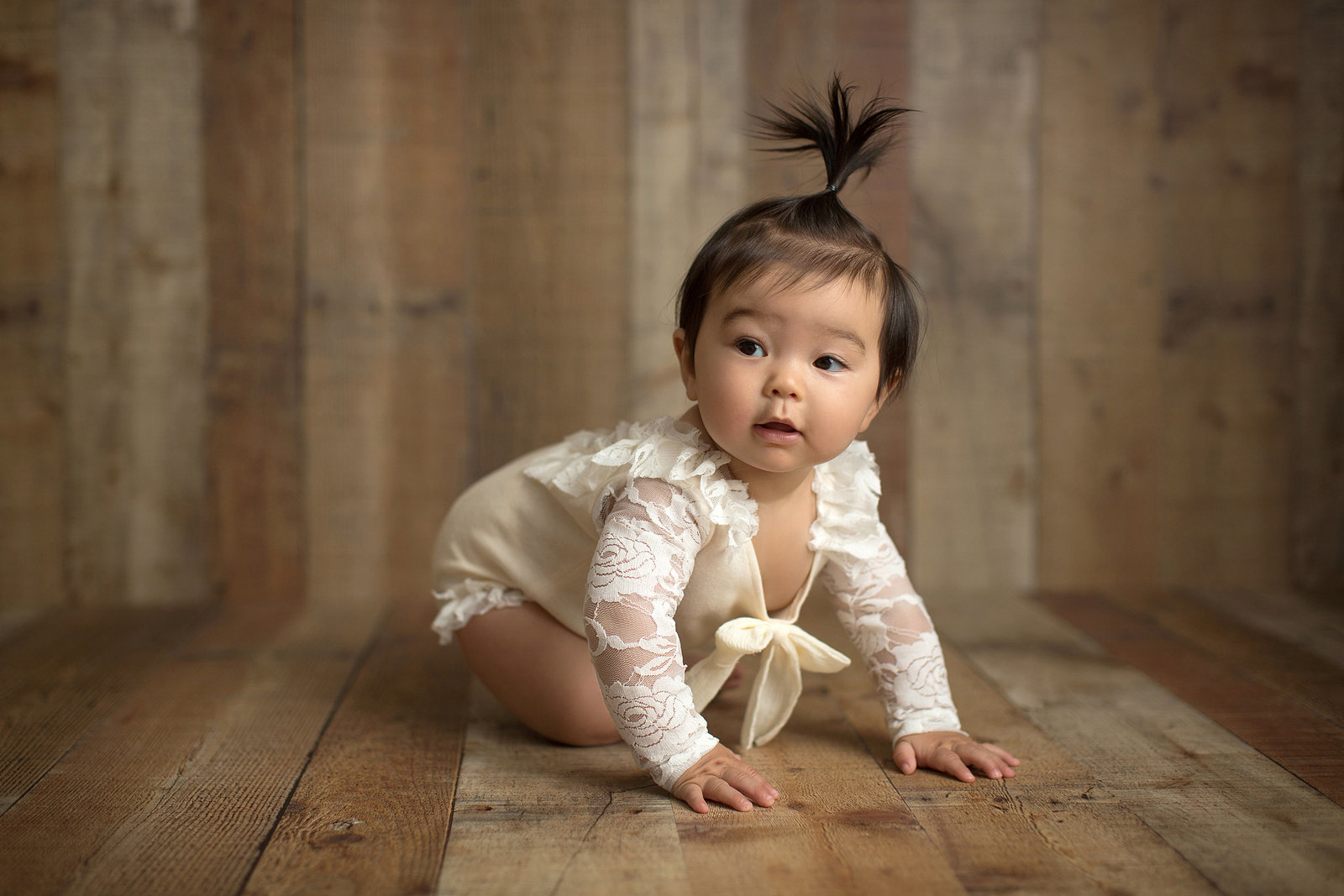 little girl in cream outfit on wood background with smile on face