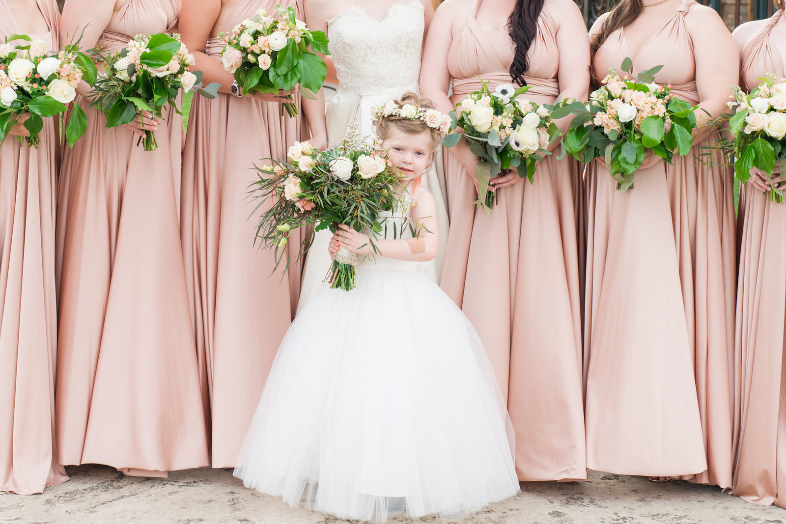Flower girl holds bridal bouquet with BHLDN bridesmaids wrap dresses behind her at Old Glory Ranch Wedding in Wimberley, Texas
