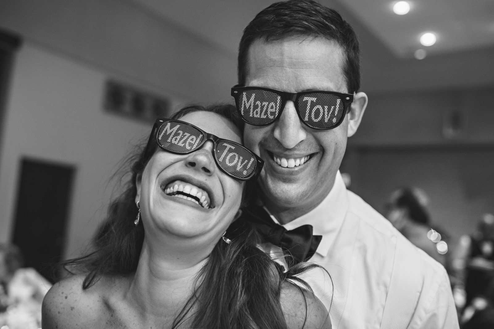 A bride and groom wearing sunglasses that say mazel tov.
