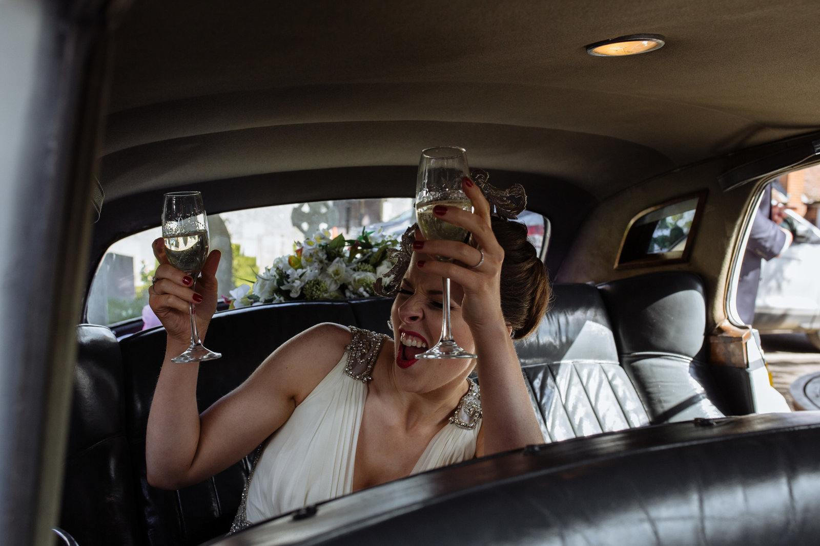 Bride in vintage car with glasses of champagne. Stoke Park wedding photographer