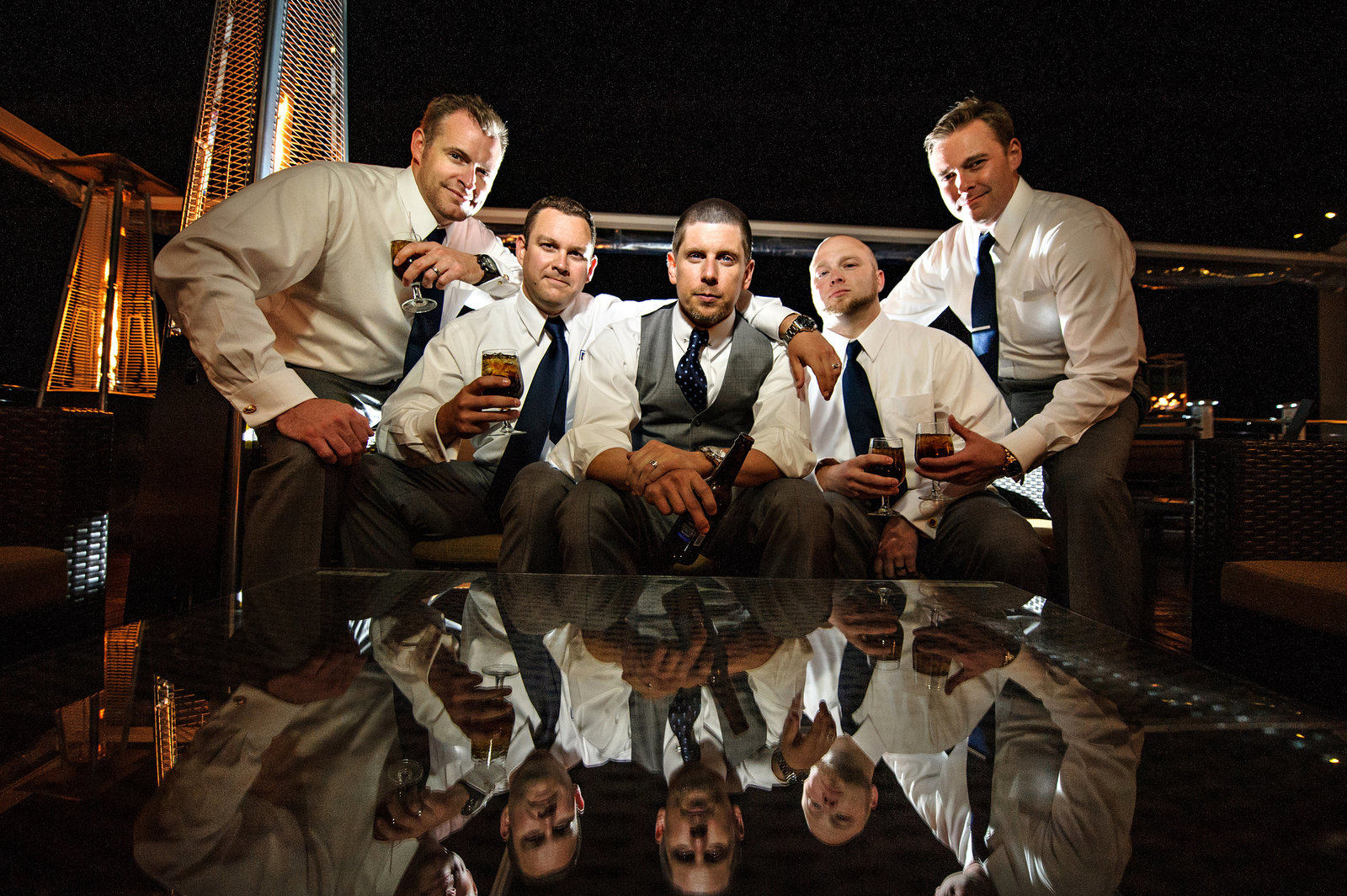 A groom and his groomsmen having a drink on the balcony of his wedding venue.