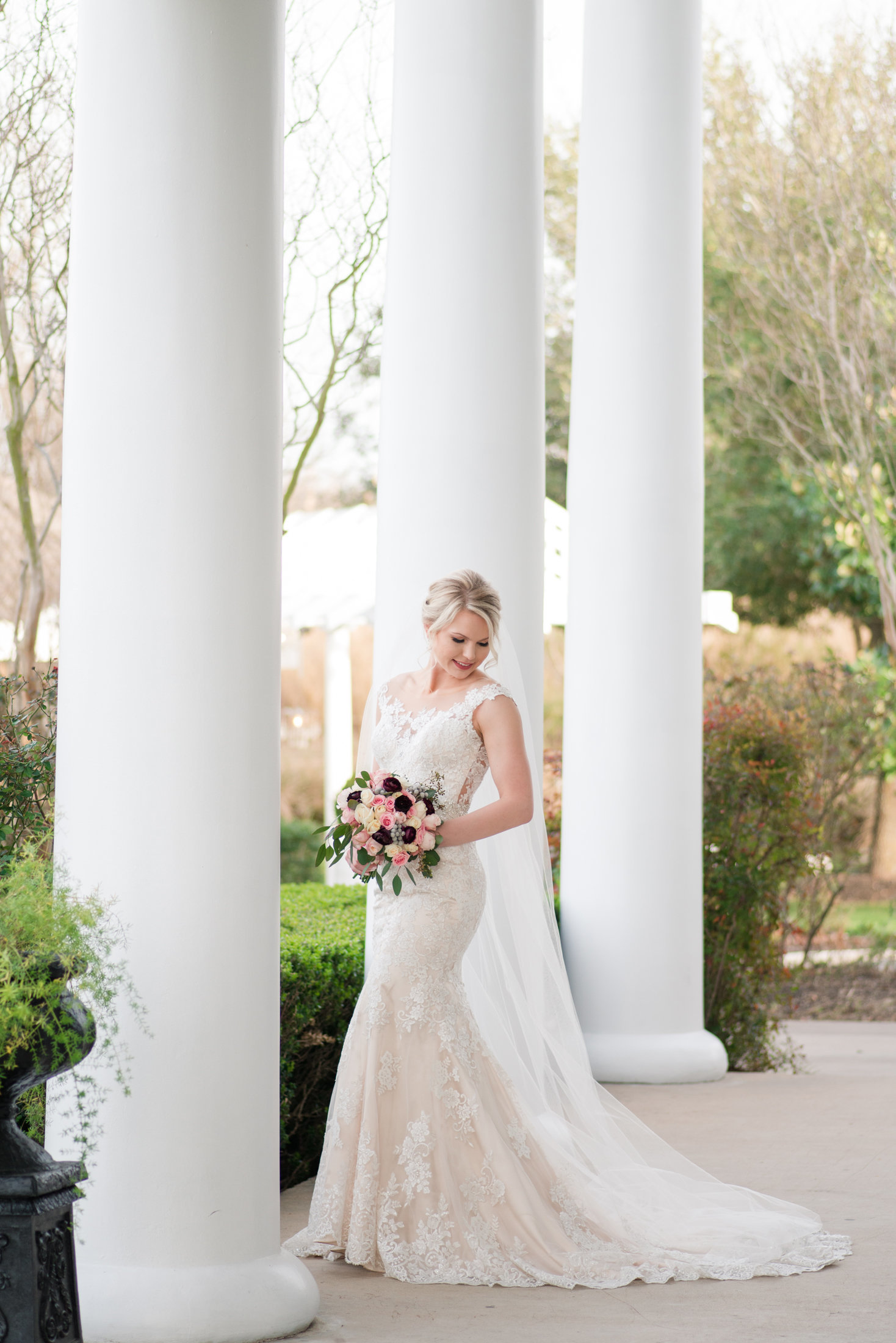Bride with blush and burgundy bridal bouquet stands on porch of the Plantation House in Pflugerville, Texas