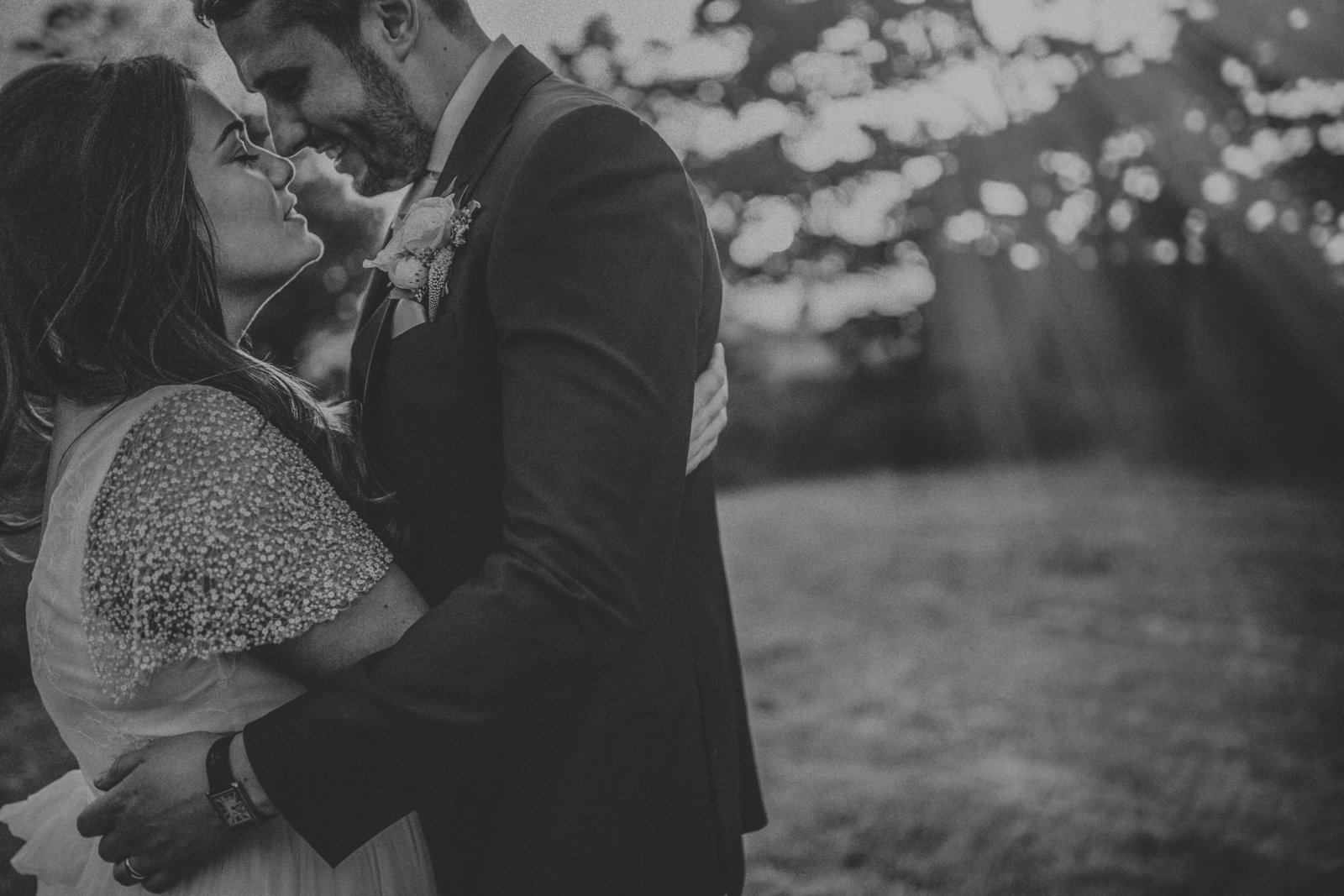 Bride & Groom hugging with back drop of sun rays coming through the tree's by Liverpool Wedding Photographer Jono Symonds