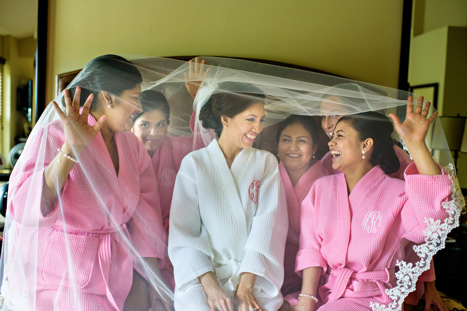 A bride and her bridesmaids under the veil in her parents home before the wedding.
