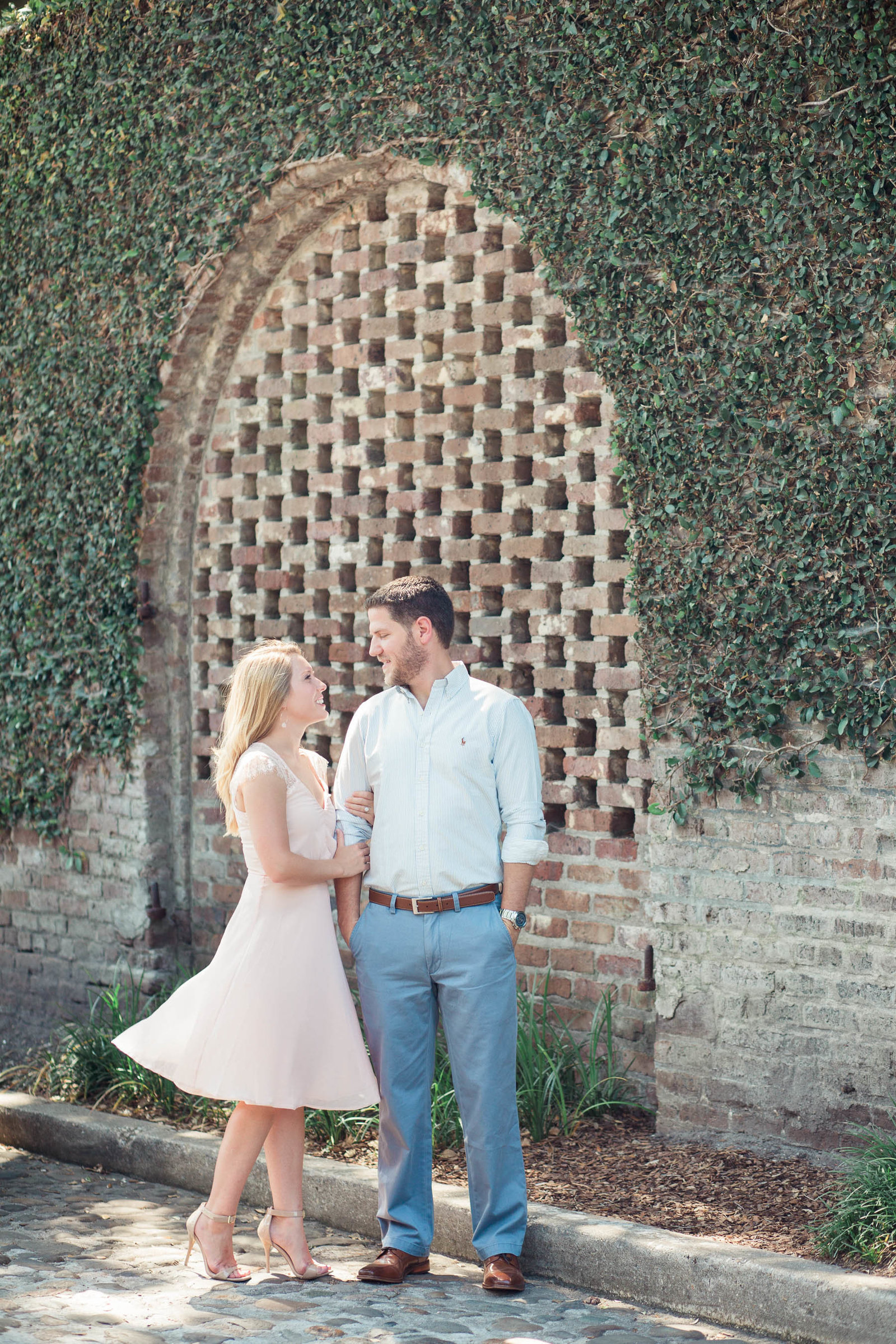 Engaged couple pose in front of red brick and ivy, Downtown Charleston Engagement Photographer.