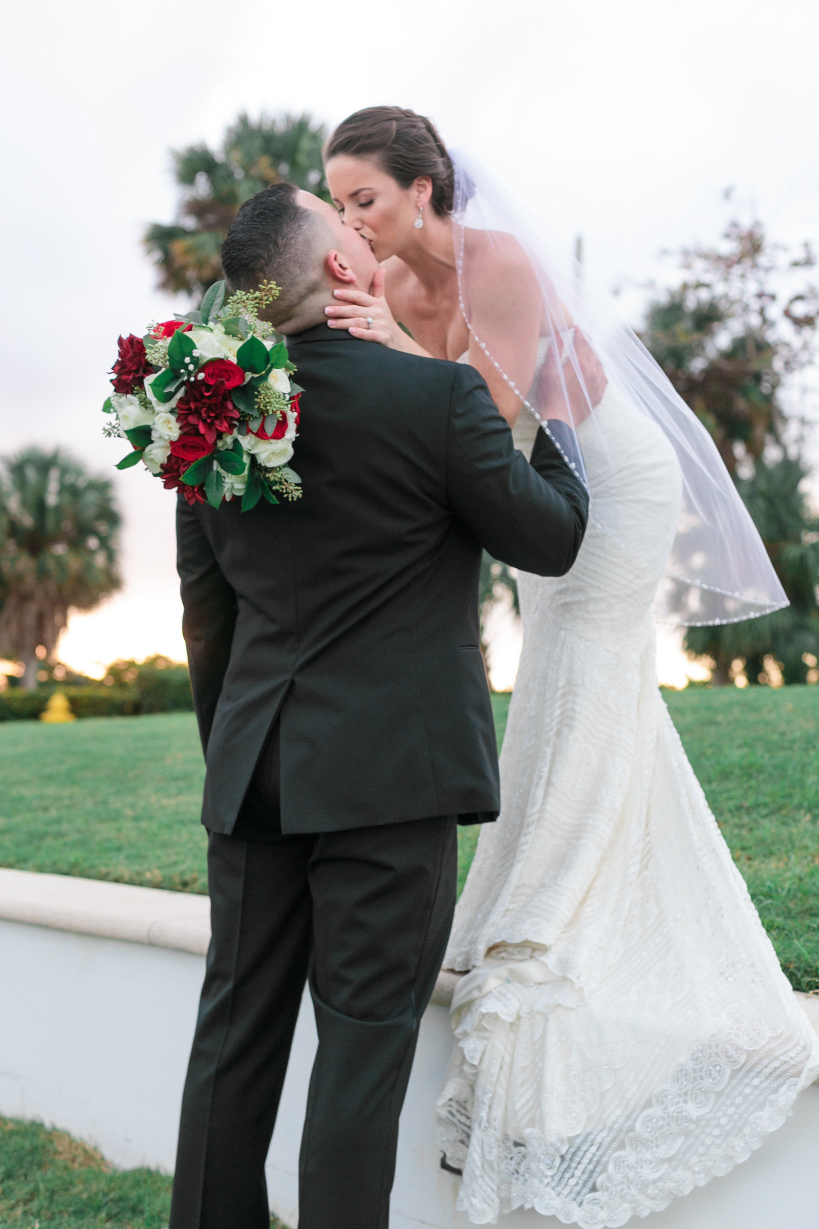 Bride kissing groom while standing on the grass