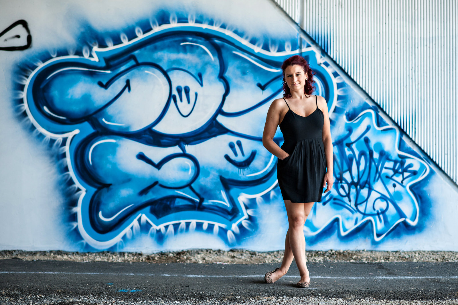 portrait of a dancer in front of a blue graffiti wall.