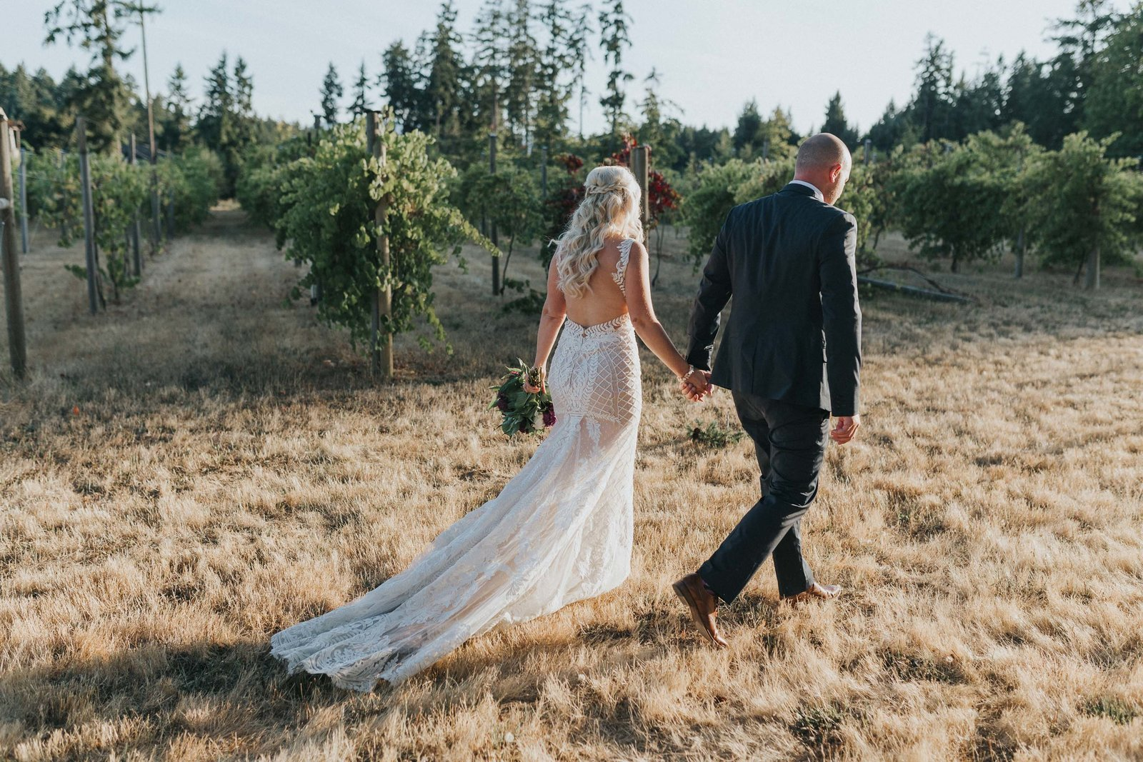 Bride and groom walking towards their vineyard wedding on Vancouver Island