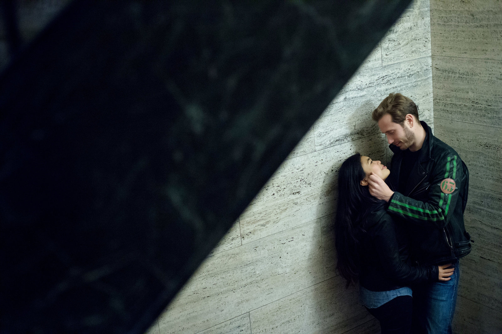a fashionable couple embrace underneath a stairwell in chicago