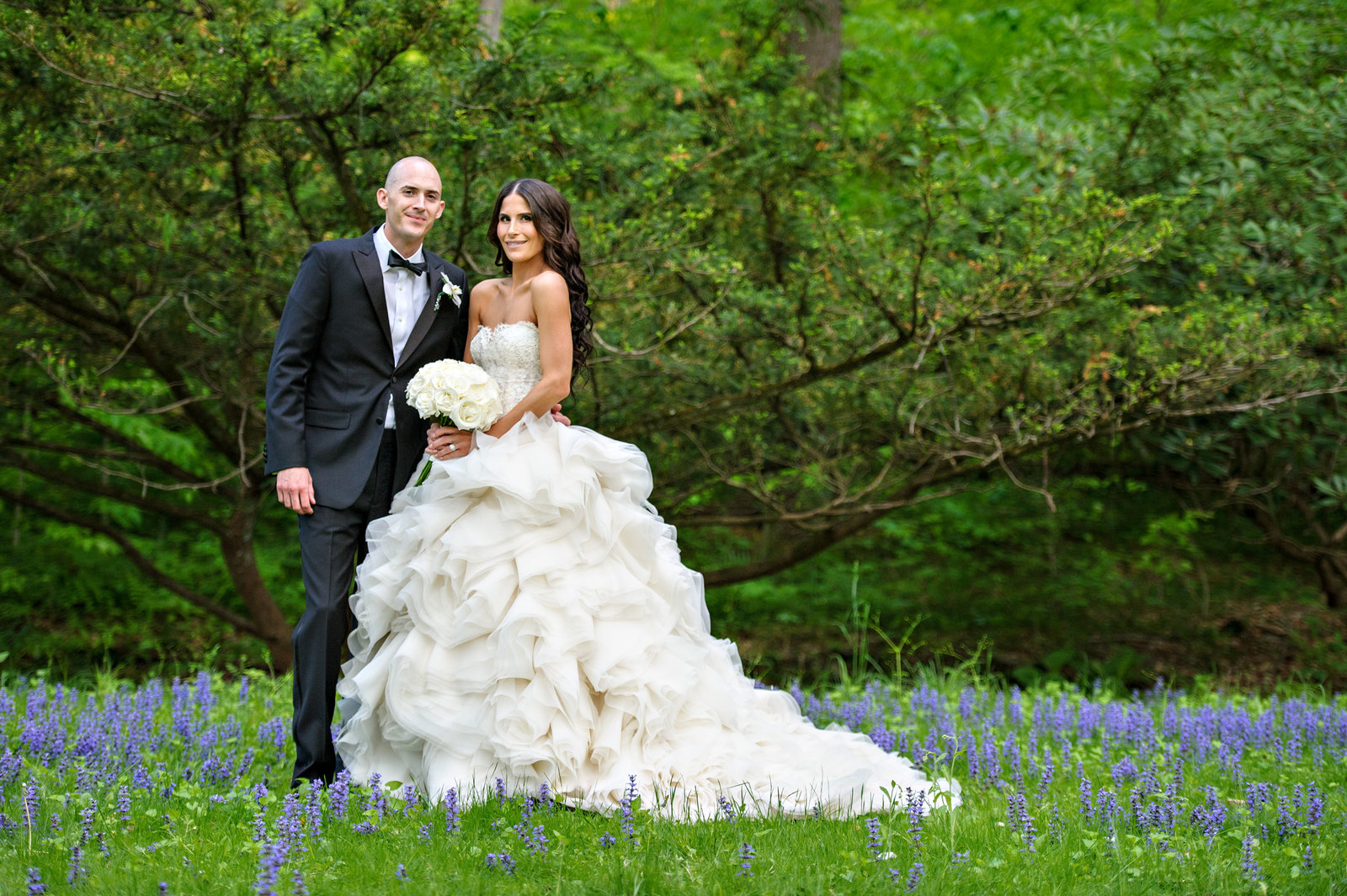 A wedding couple pose for a portrait in the flowers at Holly Hedge Estate.