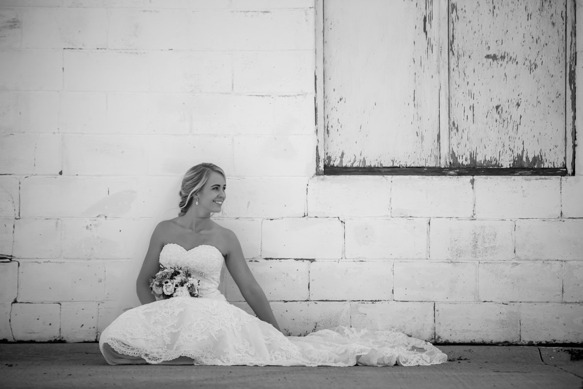 bride-sitting-by-building-black-white