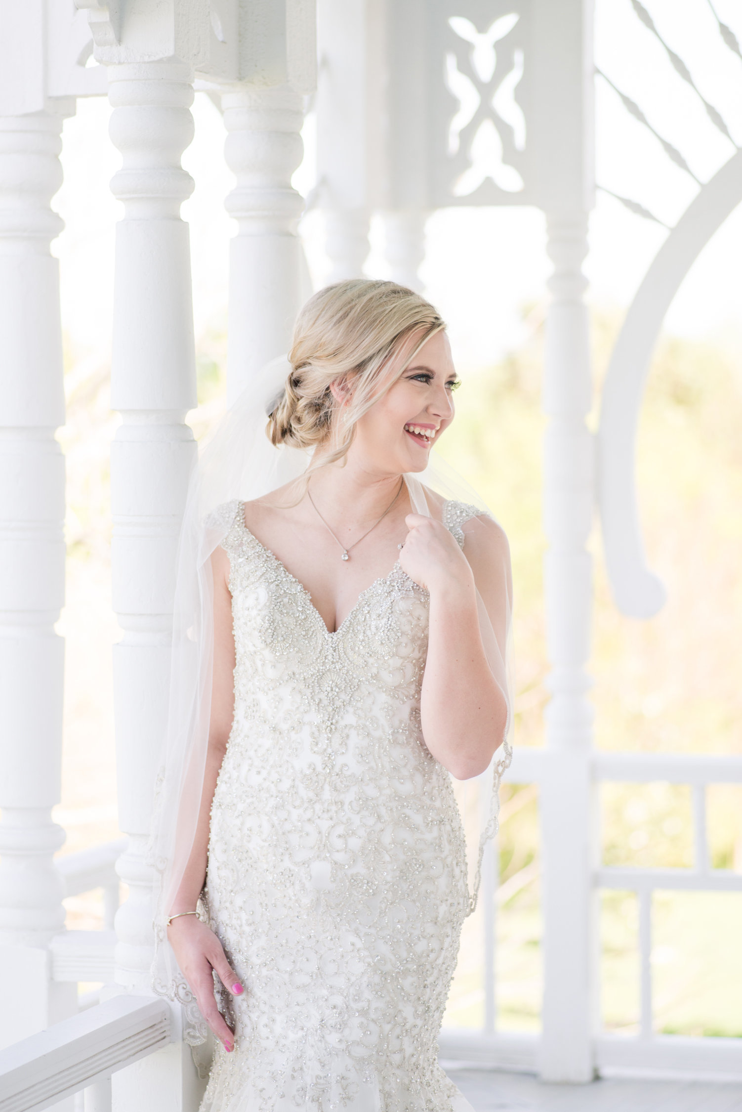 Bride smiles on balcony of The Barr Mansion in Austin, Texas