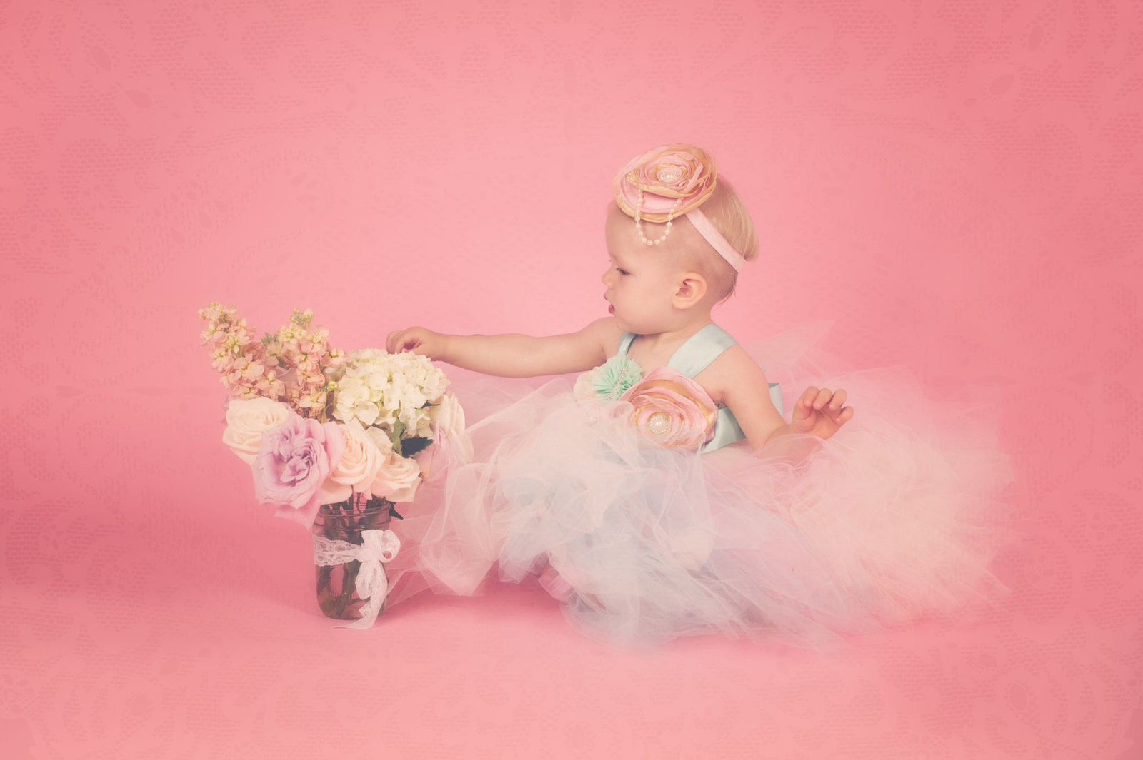 baby girl in tutu with flowers and pink background