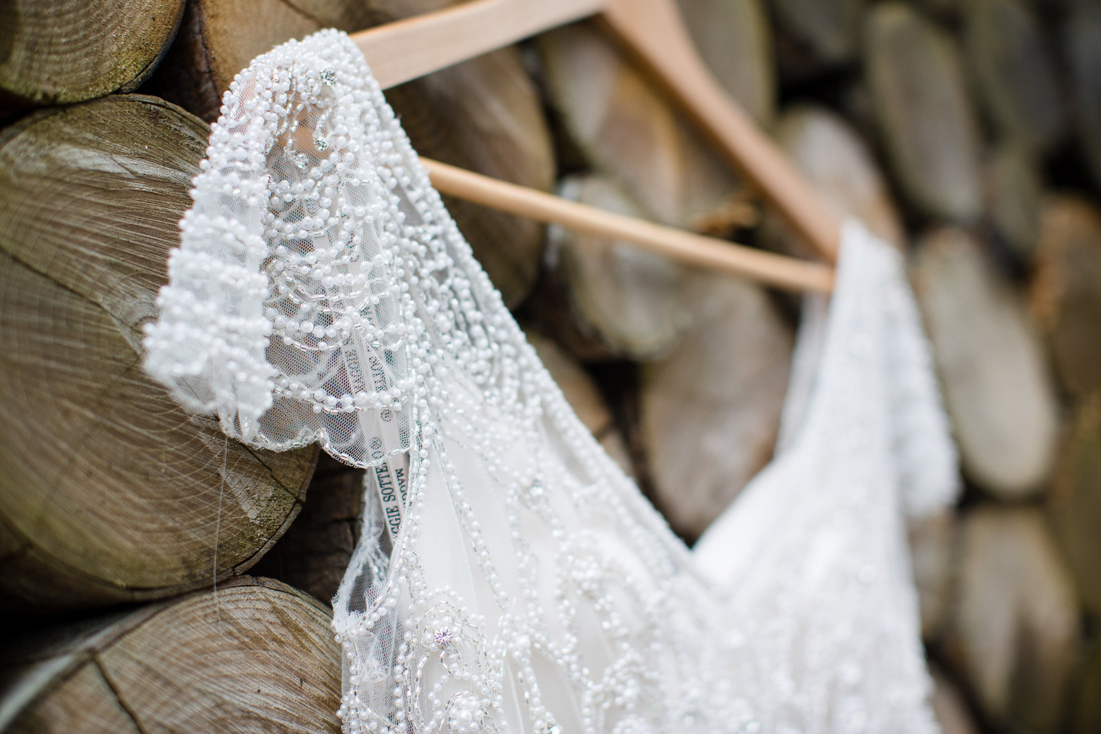 A close up of the fine beading and details of this stunning Jenny Packham  wedding dress at Southend Barns hanging on the log wall in the garden on this wedding day.