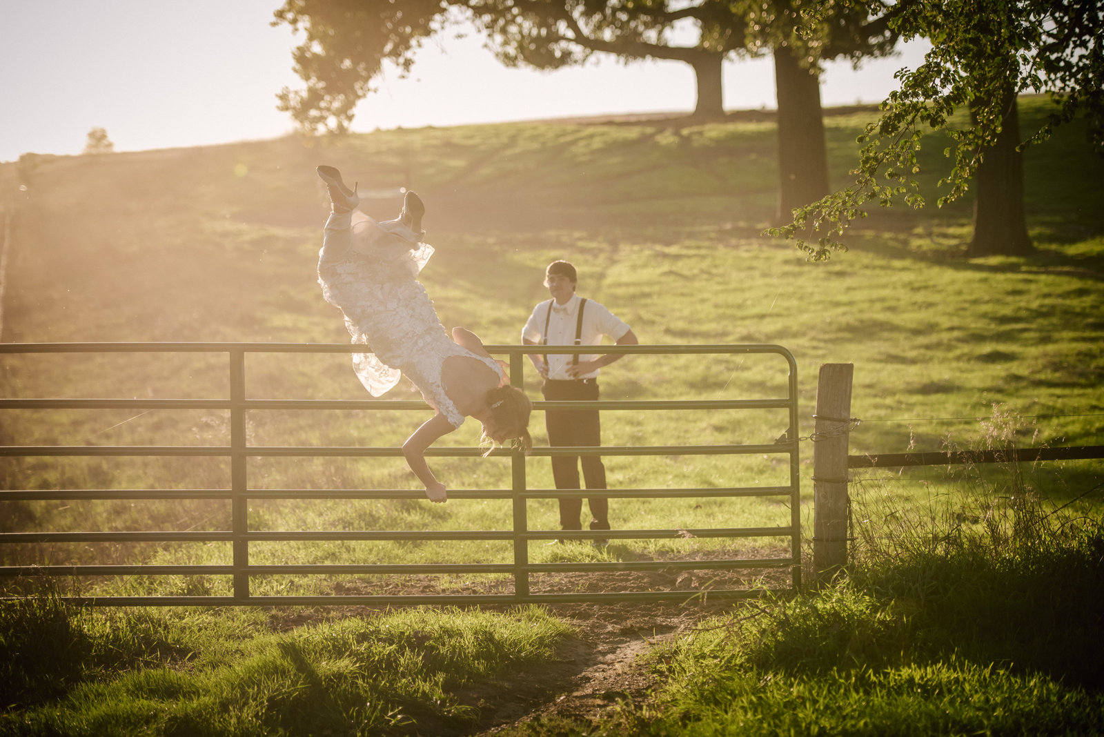 bride jumping over a fence in her wedding dress while groom watches