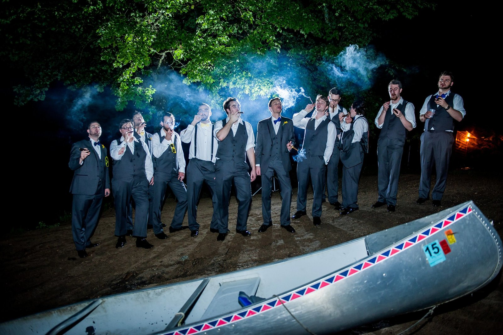 Dramatic groomsmen smoking cigars at night photographed by Kris Kandel