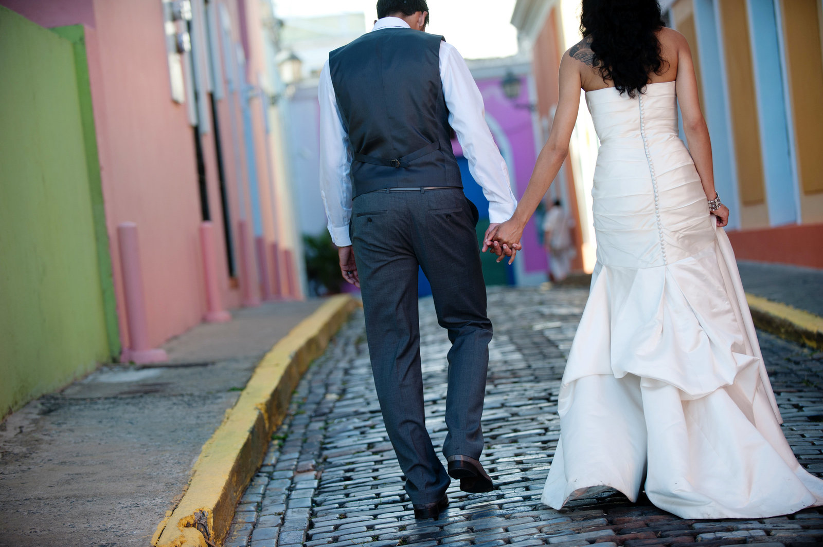 bride and groom walk down colorful cobblestone in puerto rico
