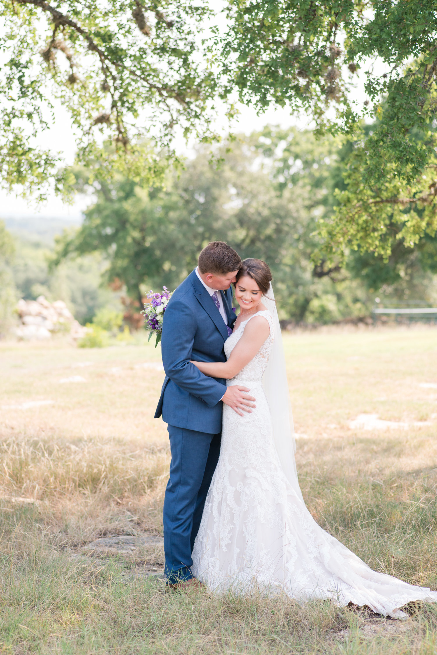 Bride and groom snuggle at purple wedding at CW Hill Country Ranch in Boerne, Texas