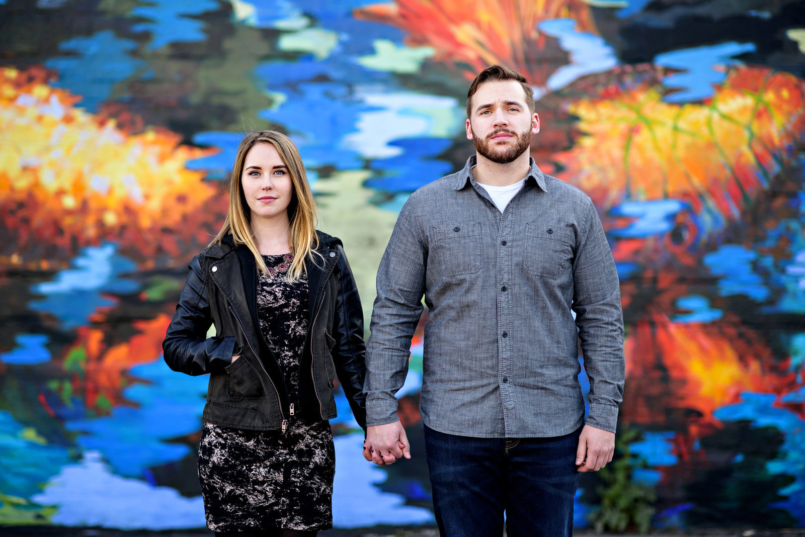 Engaged couple hold hands  in front of a graffiti wall in northern liberties.