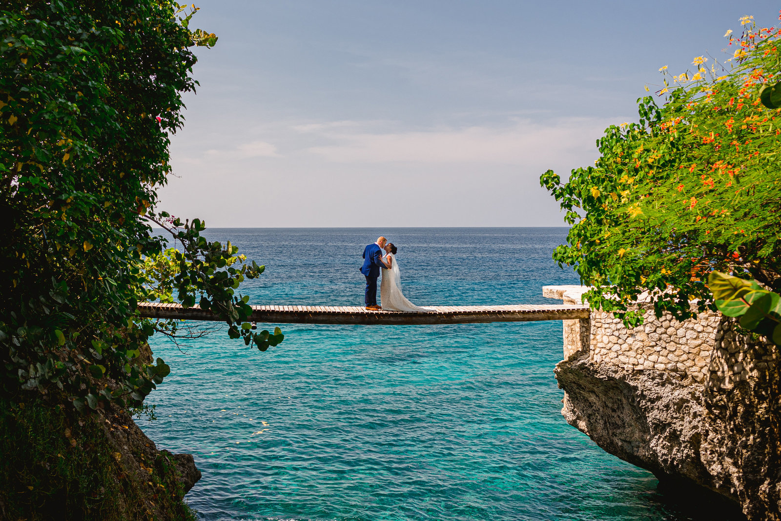 Bride & groom on a bridge in Negril Jamaica kissing