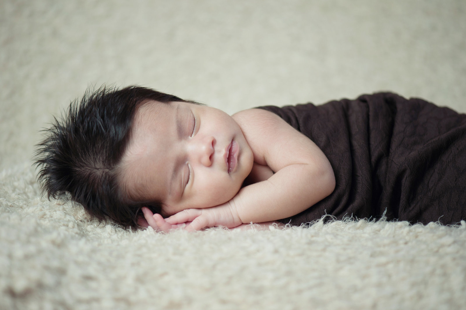 sleeping newborn wrapped in brown fabric on cream background