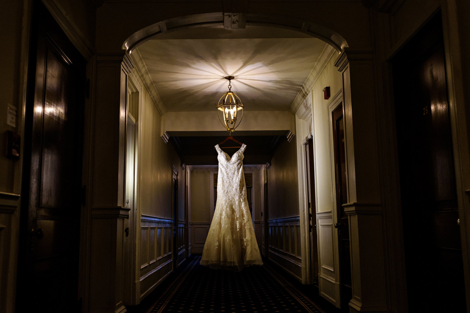A lace wedding dress hangs in the hallway of the members suites at the racquet club of philadelphia.